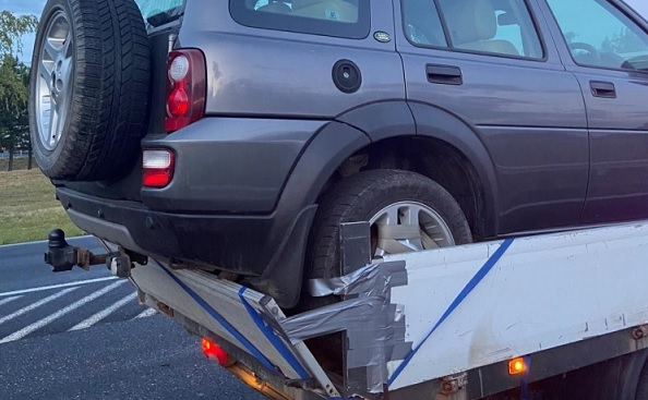 FOTÓK: Ragasztószalaggal és spaniferrel rögzítette az autót a platóra