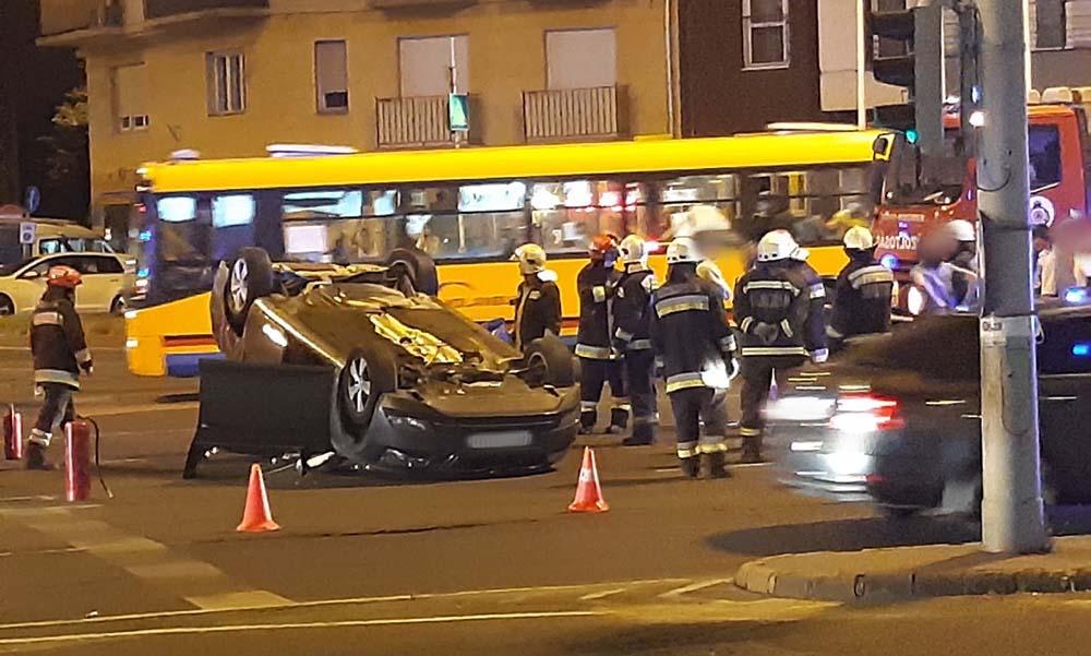 Fotók: Két jármű ütközött, az egyik felborult a Boráros téren