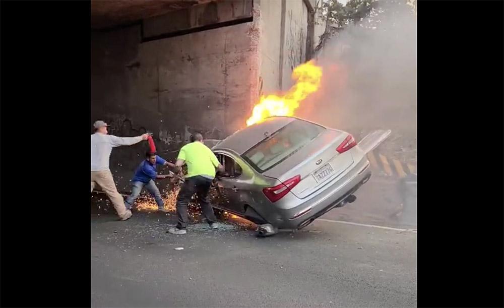 VIDEÓ: Elképesztő összefogással mentették a sofőrt és utasát a kigyulladt autóból a civilek