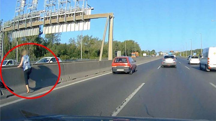 Videón, ahogy elkezd átmászni egy nő az M1-M7 elválasztó betonelemen